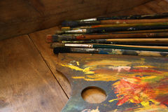 Top view of set of used paint brushes and palette over wooden table Royalty Free Stock Photo