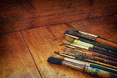 Top view of set of used paint brushes and palette over wooden table Stock Photo