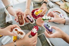 Top view of seven female hand that hold beautiful custard cakes Royalty Free Stock Photos