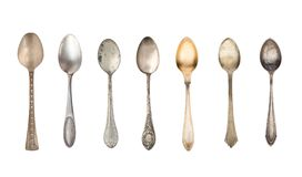 Top view of seven old silver beautiful tea spoons isolated on white background. Vintage kitchen and household items royalty free stock images
