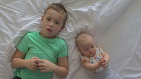 Boy and baby girl siblings on bed at home stock footage