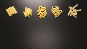 TOP VIEW: Several pasta types fill on a black table stop motion stock footage