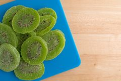 Slices of glazed kiwi fruit on a blue cutting board Stock Photography