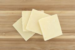 Sharp cheddar cheese on a small cutting board Stock Images
