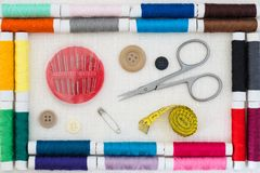 Sewing kit colorful threads frame top view white linen background. Top view of a sewing kit in a frame of colorful threads: a box with assorted needles, buttons Royalty Free Stock Images