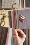 Top view of sewing table with fabrics, supplies for home decor or quilting project and woman`s hand Stock Photos