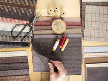 Top view of sewing table with fabrics, supplies for home decor or quilting project and woman`s hand. Top view image of sewing table with pretty pastel fabrics Royalty Free Stock Photos