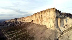 Top view of sheer cliff. Shot. Amazing panoramic view of steep white rock with erosion at its foot. White mountain with stock video