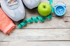 Top view shoe,measuring tape,green apple,alarm clock and towel on wood table background royalty free stock photography