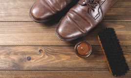 Top view of shoes and cleaning products on brown wooden table. Royalty Free Stock Photo