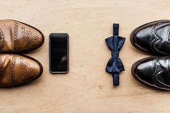 Shoes, smartphone and tie bow on wooden surface. Top view of shoes, smartphone and tie bow on wooden surface Stock Image