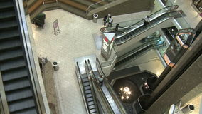 Top view of shoppers in mall near escalators and elevators (2 of 2). A view or scene of Shopping stock video