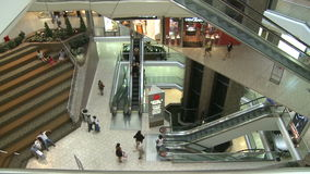 Top view of shoppers in mall near escalators and elevators (1 of 2). A view or scene of Shopping stock video footage