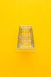 Top view of shopping trolley on yellow Royalty Free Stock Photos