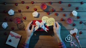 Adult man puts valentine heart onto the gift box, top view. Top view shot of male hands putting paper valentine heart onto the gift box for valentine day stock video footage