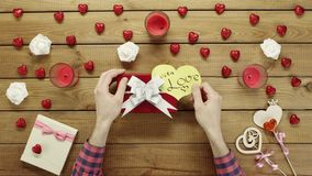 Man puts valentine heart onto the gift box, top view. Top view shot of male hands putting paper valentine heart onto the gift box for valentine day stock video