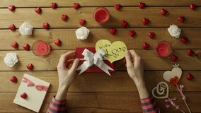 Young man puts valentine heart onto the gift box, top view. Top view shot of male hands putting paper valentine heart onto the gift box for valentine day stock video