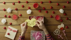 Young man gets handmade paper valentine heart as valentine day present, top view. Top view shot of male hands unboxing gift box with handmade paper valentine stock video