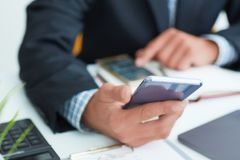 Top view shot of a man`s hands in suit using smart phone in office interior, business man hands using cell phone at stock photos
