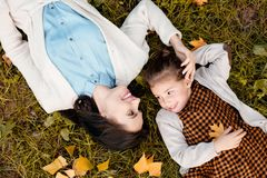 Top view shot of mother and little daughter lying on grassy. Lawn stock photos
