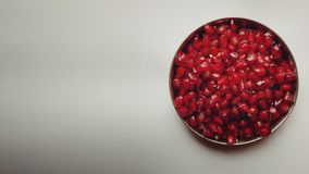 Top view shot of pomegranate seeds in plate on a white background. stock photography