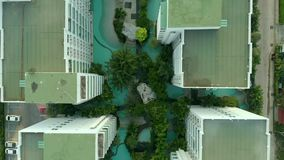 Top view shot. Swimming pools surrounding palms and green garden in the beautiful tropical aerial top view. Top view shot. Swimming pools surrounding palms and stock video