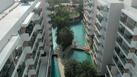 Top view shot. Swimming Pools surrounding palms and green garden in the beautiful tropical aerial top view. Top view shot. Swimming Pools surrounding palms and stock video footage