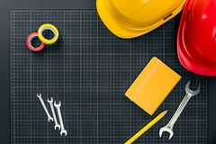 Tools and hardhats on graph paper Stock Image