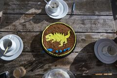 Top view shot of a yellow t-rex chocolate birthday cake on a wooden table