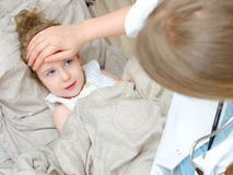 Top view of sick child lying in bed Stock Images