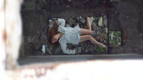 Top view at the sick woman patient in white shirt lying on the ruins of the abandoned mental hospital. Top view at the sick woman patient in white shirt lying stock video