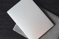 Top view on the silver laptop with grey case. On the wooden desk. Minimalistic background stock photo