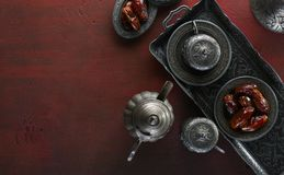 Top view on silver plate with date fruits and coffee cups on the dark red wooden background. Ramadan background. Ramadan kareem royalty free stock photo