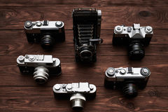 Top view of six retro cameras over wooden background Royalty Free Stock Image
