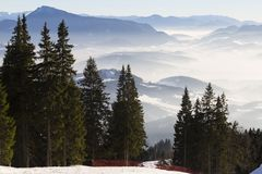 Top view from the ski slopes among the spruces on snow covered a. Nd foggy valley on the background mountain peaks. Skiing park Kubinska Hola; Western Tatras stock image