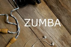 Top view of skipping rope,earphone and water bottle on wooden background written with Zumba. Health and fitness concept. stock photos