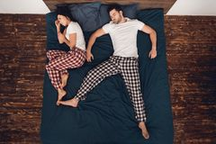 Top view. Sleeping adult man lies on bed with his leg thrown to side of sleeping woman. Top view. Sleeping adult men lies on bed with his leg thrown to side of Royalty Free Stock Images