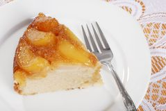 Top view slice of upside down pear cake. With A Fork with white tablecloth Royalty Free Stock Image