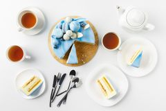 Top view of sliced cake on chopping board with tea cups and plates. Isolated on white stock photo