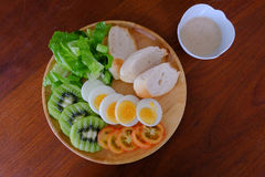 Top view of Sliced egg salad serve with vegetable, kiwi, tomato, crispy bread and separated Japanese sesame dressing stock photos