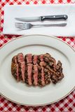 Top view of Sliced medium rare charcoal grilled wagyu Ribeye steak in white plate on red and white pattern tablecloth with cutlery Royalty Free Stock Photos