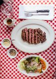 Top view of Sliced medium rare charcoal grilled wagyu Ribeye steak in white plate on red and white pattern tablecloth. Royalty Free Stock Images