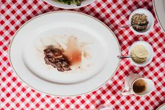 Top view of Sliced medium rare charcoal grilled wagyu Ribeye steak in white plate on red and white pattern tablecloth. Stock Image