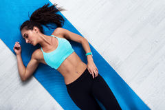 Top view of slim fitness model lying on mat resting after workout royalty free stock photos