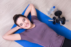 Top view of slim woman lying on yoga mat after training Stock Images