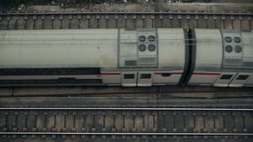 Top view slow motion on trains. Top view on railroad tracks with double deck passenger mid distance train slowly passing by in central lane from left to right stock video footage