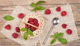 Top view of small basket with fresh raspberries with leaves. View from above of wicker basket with raspberries on wooden table Royalty Free Stock Images