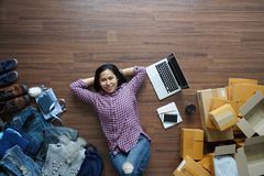 Top view small business owner woman lying on wooden floor. With postal parcel, Online selling, e-commerce, shipping ideas concept royalty free stock photo