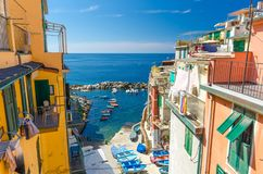 Top view of small harbor with fishing colorful boats, multicolored houses with balconies and shutter windows of Riomaggiore villag royalty free stock photos