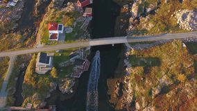 Top view of the small houses, rocks and boat under a bridge. Norway stock video